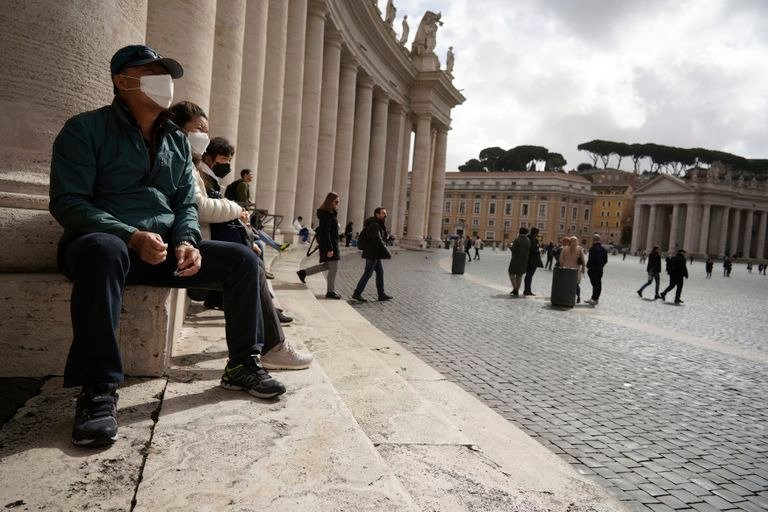 People sit by Bernini's colonnade in St. Peter's Square at the Vatican, Friday, March 6, 2020. A Vatican spokesman has confirmed the first case of coronavirus at the city-state. Vatican spokesman Matteo Bruni said Friday that non-emergency medical services at the Vatican have been closed so they can be sanitized following the positive test on Thursday. (AP Photo/Andrew Medichini)